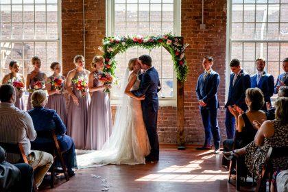 newlyweds first kiss floral wedding arch