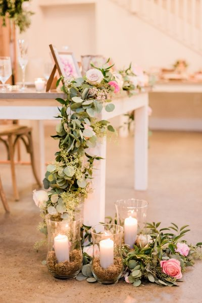 Gorgeous sweetheart table with florals and candles