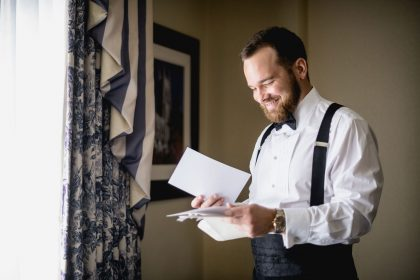 Groom reading letter from bride pre-ceremony