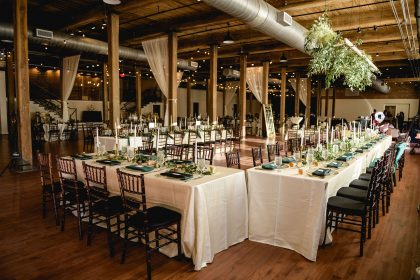 green and white centerpieces with draping in background wedding reception