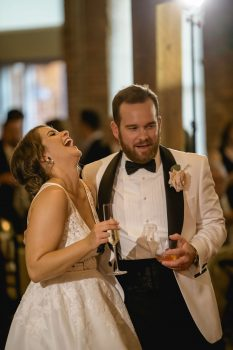 Laughing bride and groom in white tux jacket