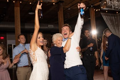 Grandma with newlyweds on dance floor at wedding reception