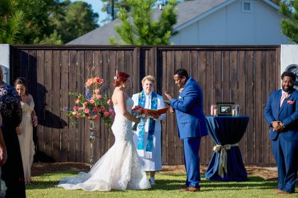 outdoor wedding ceremony with pink and beach florals