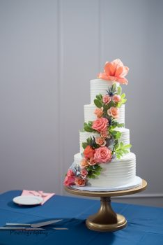 Pastry Works 4 tier white wedding cake with peach pink and green florals