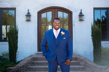groom in blue suit with peach and pink boutonnière and tie