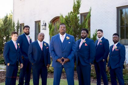 groom and groomsmen in blue suits with pink and peach accents