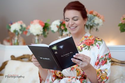 bride reading book made by groom before wedding