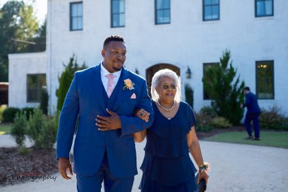 mother of the groom and son walking down aisle outdoor ceremony
