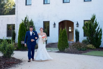 brother walking sister down the aisle in front of French Country wedding venue
