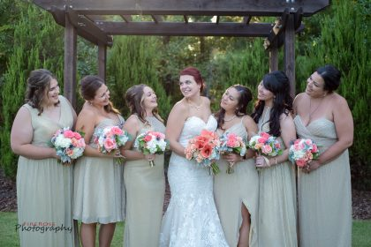 bridesmaids in sage green with peach, pink and white bouquets