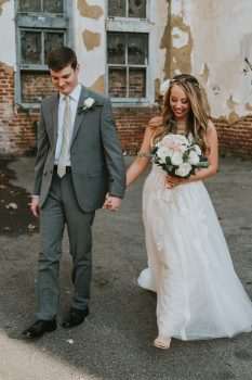 Groom in Gray Suit and Bride with white flowers and antique white dress