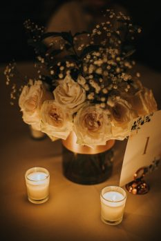 Candle lit centerpieces with white roses and baby's breath