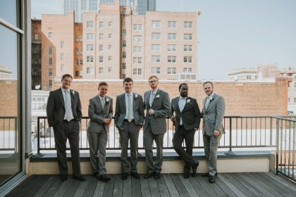 groom and groomsmen in gray suits in urban setting