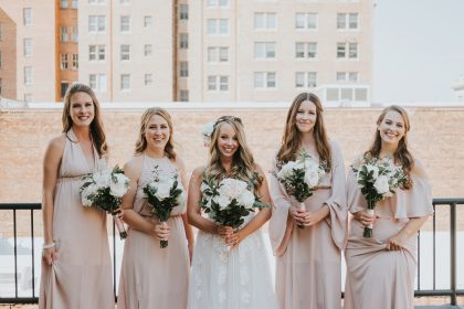 Bridesmaids in light pink dresses with white flowers