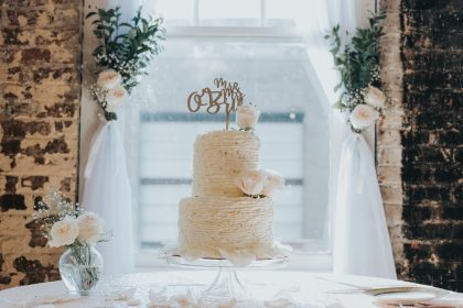beautiful white cake with white flowers and sheer curtains